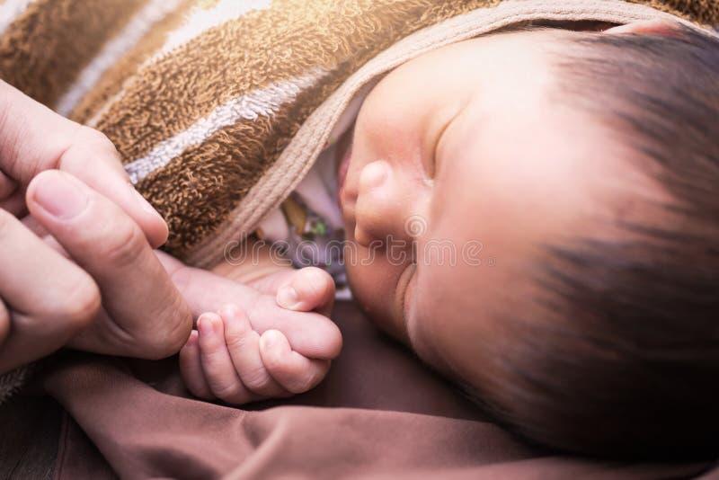 Vader die een hand van haar baby op bont houden stock afbeeldingen