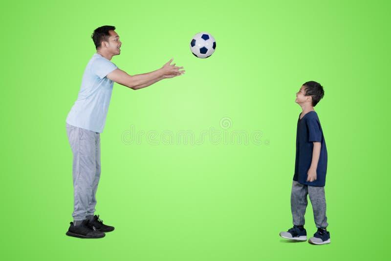 Vader die een voetbalbal werpen aan zijn zoon op studio royalty-vrije stock foto