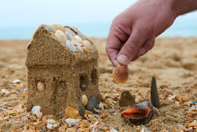 Vader die een zandhuis bouwt op een kust
