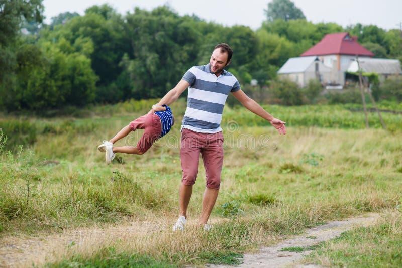 Vader die en met zijn zoon in park spelen spinnen royalty-vrije stock foto