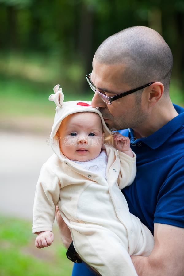 Vader die en zijn kleine dochter houden kussen stock fotografie