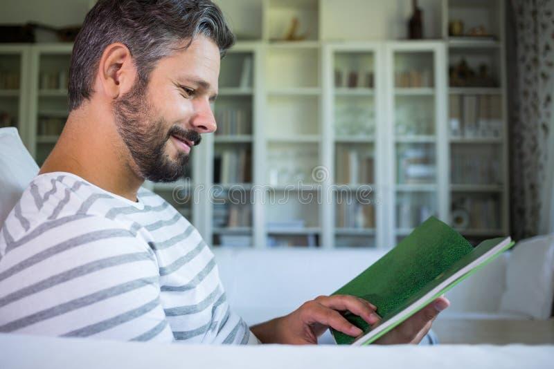 Vader die fotoalbum bekijken in woonkamer stock foto's