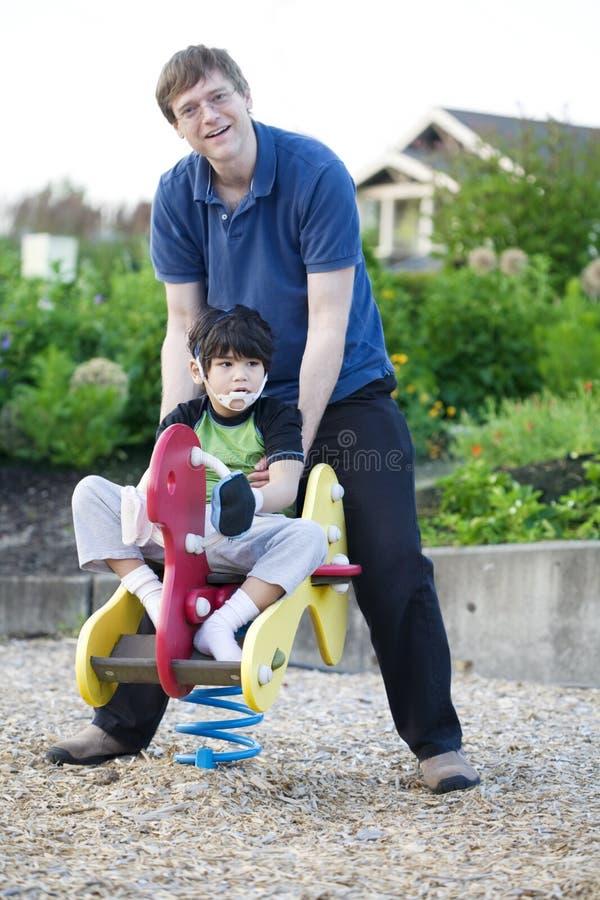 Vader die gehandicapt zoonsspel helpt bij speelplaats royalty-vrije stock afbeeldingen