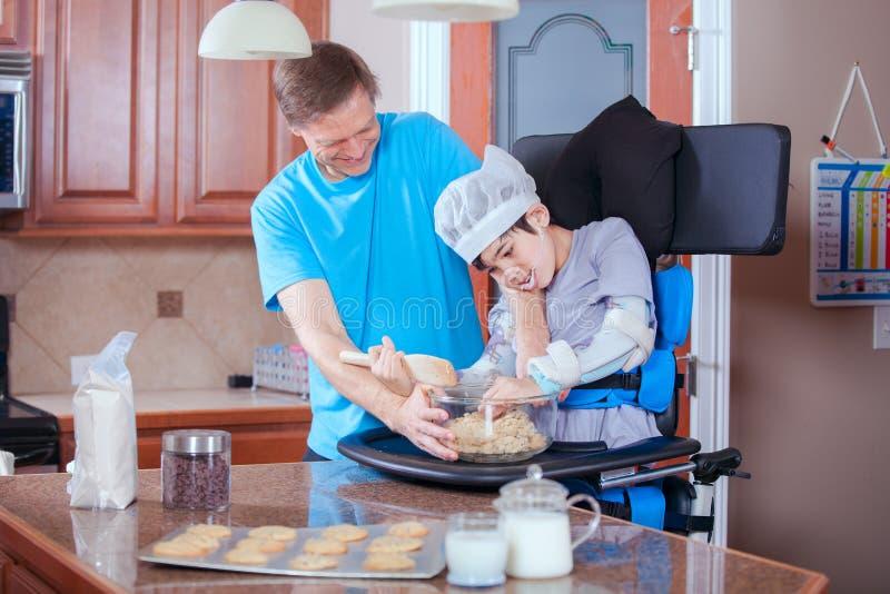 Vader die gehandicapte zoon helpen koekjes in keuken bakken stock fotografie