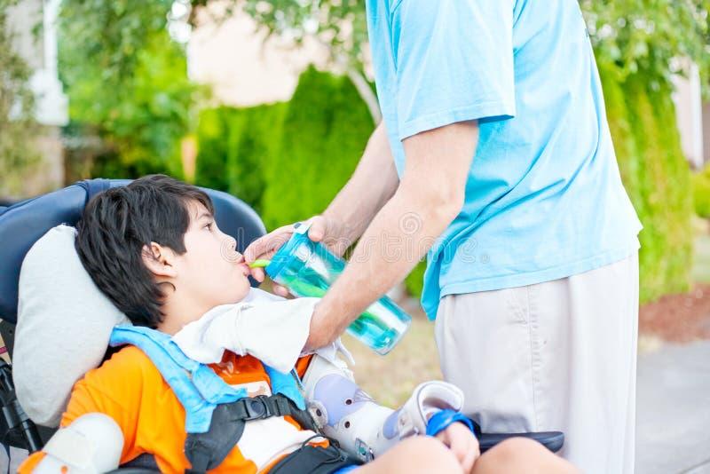 Vader die gehandicapte zoon in rolstoel helpen drank van strokop stock foto