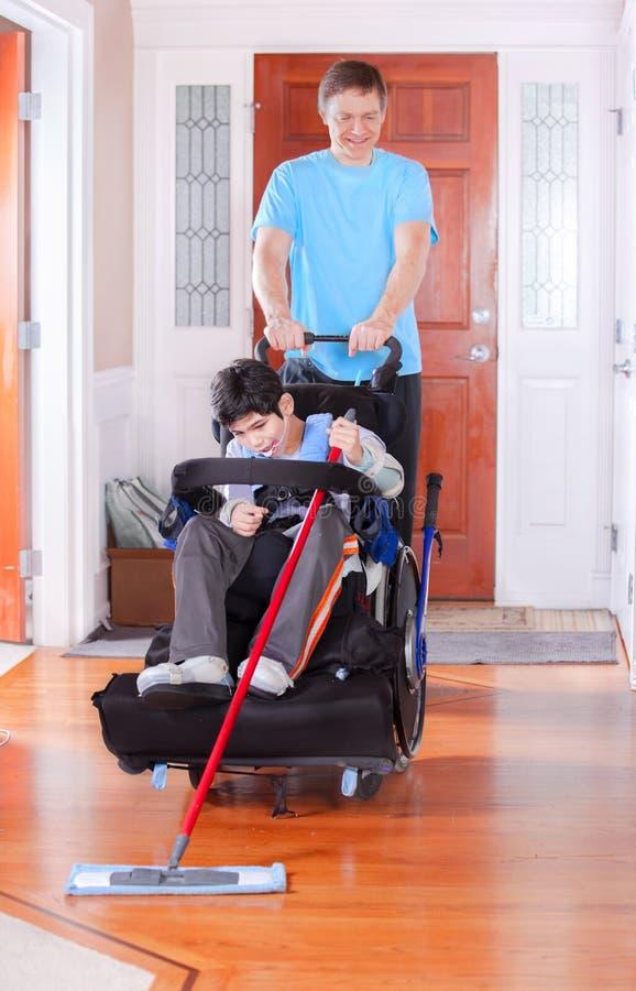 Vader die gehandicapte zoon in rolstoel helpen zwabber de vloer royalty-vrije stock foto