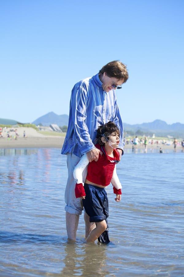 Vader die gehandicapte zoonsgang in oceaangolven helpen stock afbeelding