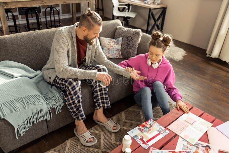 Vader die geregelde broeken dragen die dochterkalmeringsmiddelen geven royalty-vrije stock foto's