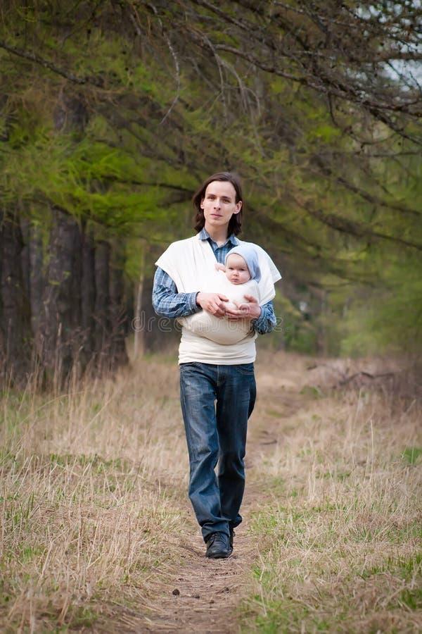 Vader die met dochter in slinger loopt royalty-vrije stock foto