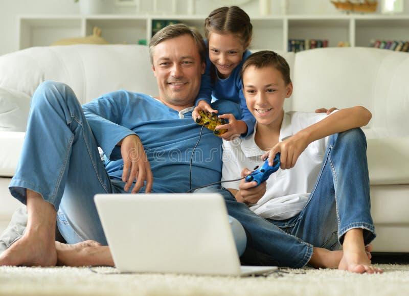 Vader die met jonge geitjes computerspelen spelen stock foto's