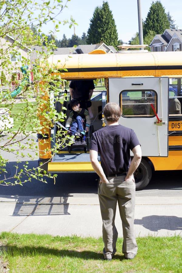 Vader die op gehandicapte zoon van schoolbus te krijgen wachten royalty-vrije stock foto