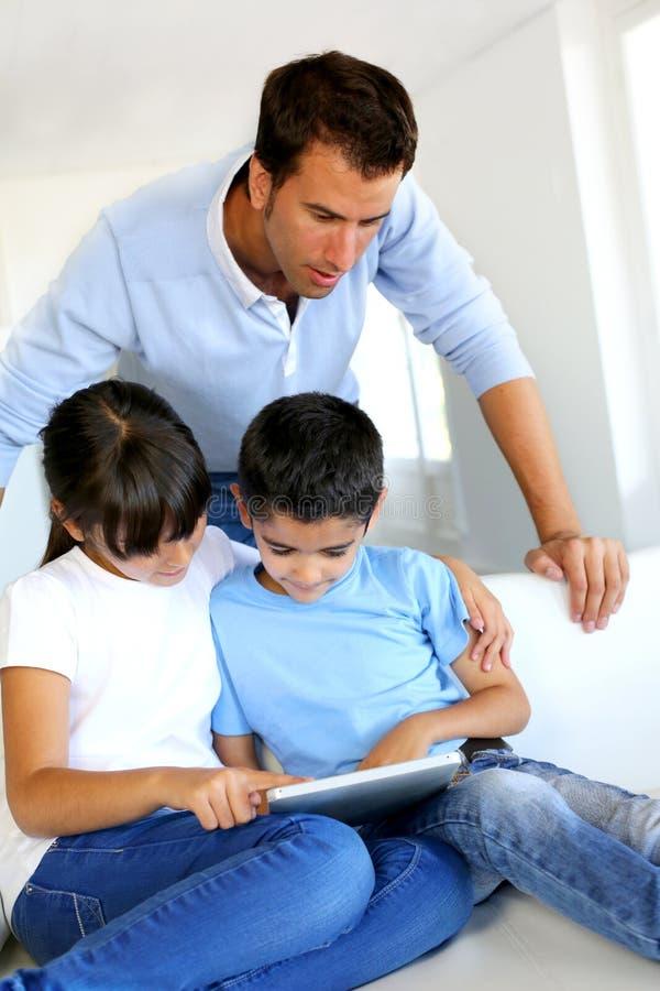 Vader die op over kinderen letten die tablet gebruiken royalty-vrije stock afbeeldingen
