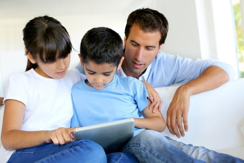 Vader die op over kinderen letten die tablet gebruiken royalty-vrije stock fotografie