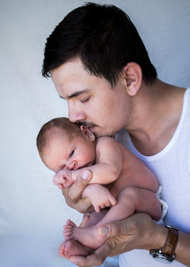 Vader die pasgeboren baby dicht bij zijn gezicht tegenhouden royalty-vrije stock afbeeldingen
