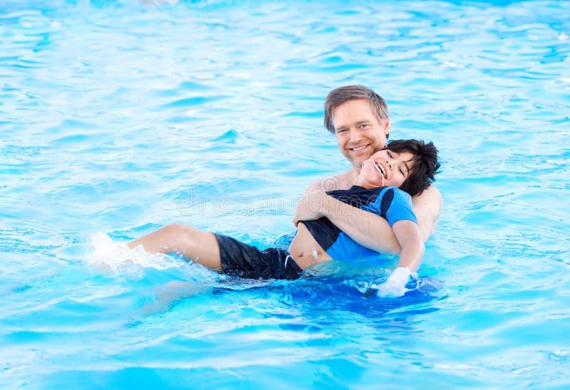 Vader die in pool met gehandicapt kind zwemmen stock foto's