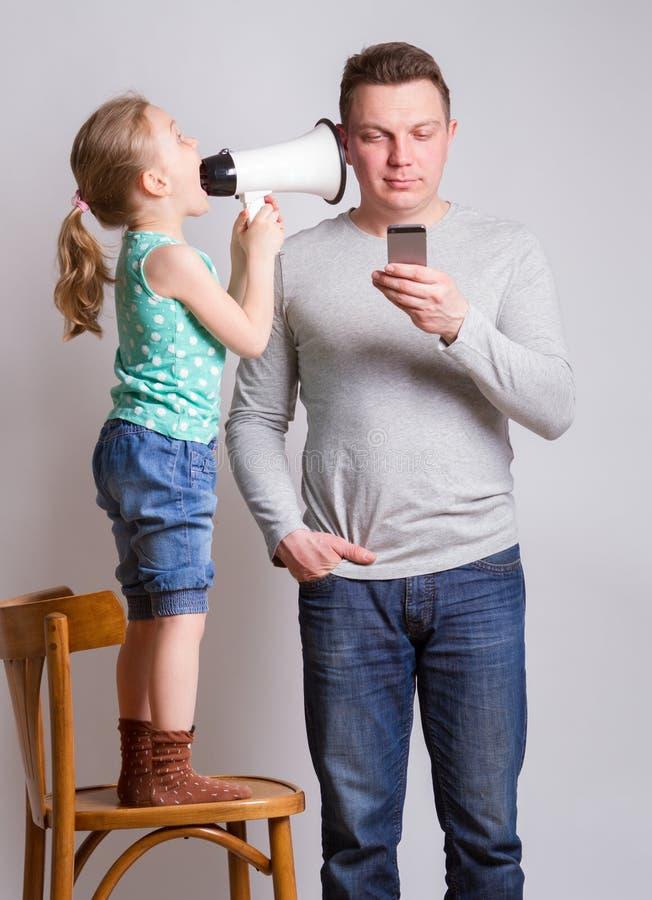 Vader die smartphone gebruiken die zijn dochter negeren stock fotografie