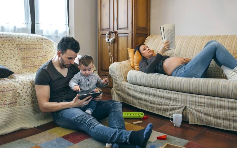 Vader die tablet met weinig zoon kijken terwijl de zwangere moeder een tijdschrift leest royalty-vrije stock fotografie