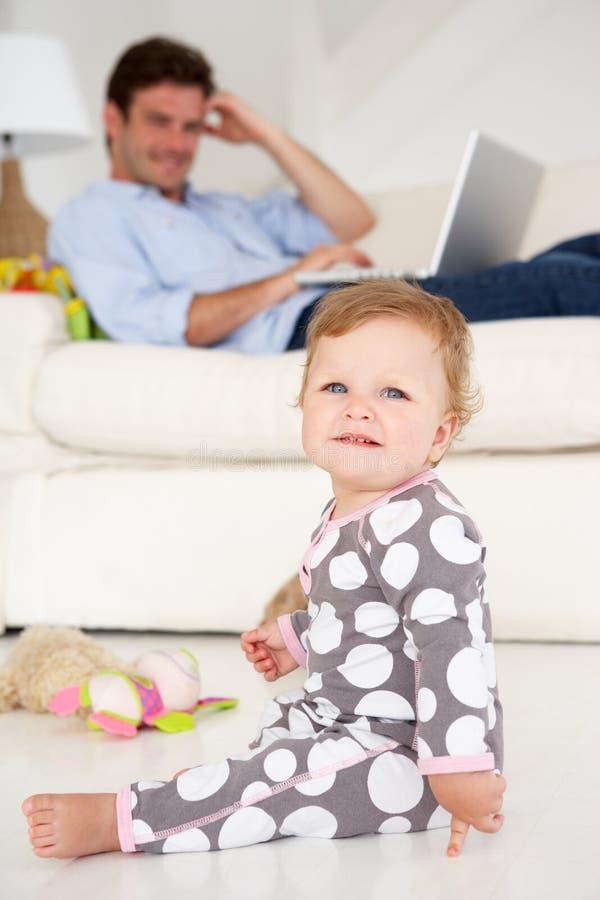 Vader die thuis terwijl het zorgen van voor kind werkt stock foto
