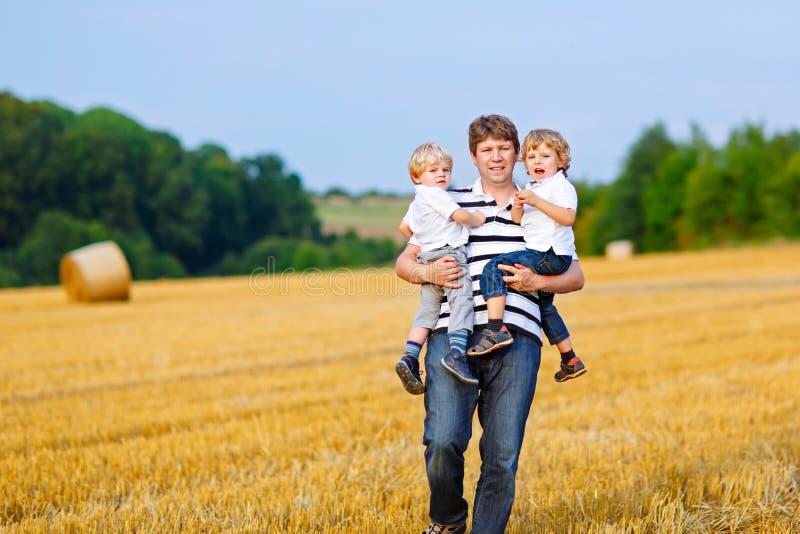 Vader die twee kinderen op wapens op tarwegebied houden in de zomer royalty-vrije stock afbeeldingen