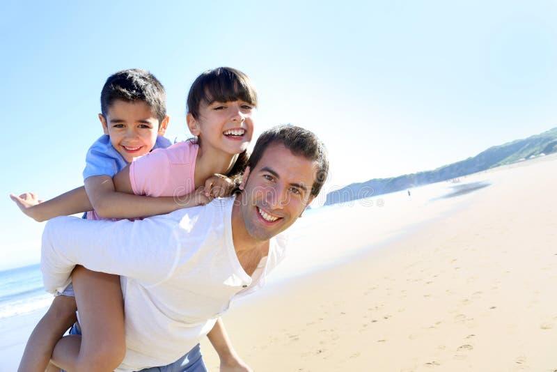 Vader die twee kinderen op zijn rug op het strand vervoeren stock foto's