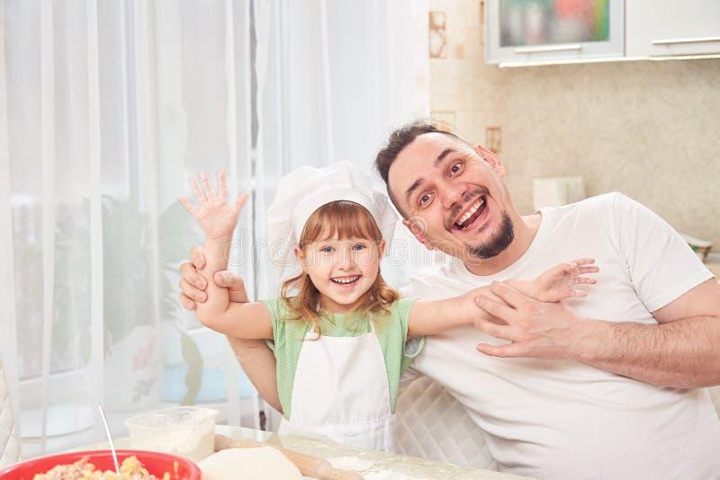 Vader die voedsel met mijn dochter voorbereiden de man glimlacht gelukkig samen met haar dochter standhield haar wapens Positieve royalty-vrije stock foto