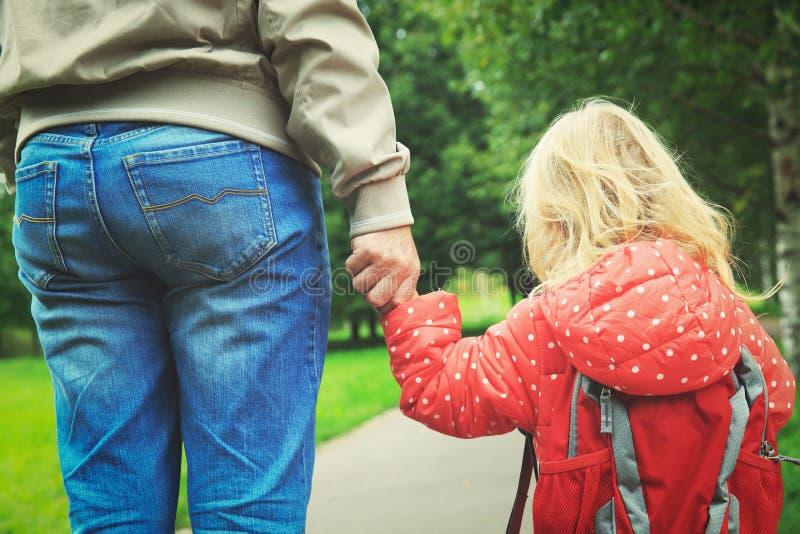 Vader die weinig dochter lopen aan school of opvang stock foto