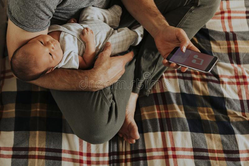 Vader die zijn baby houden terwijl het gebruiken van zijn telefoon stock fotografie