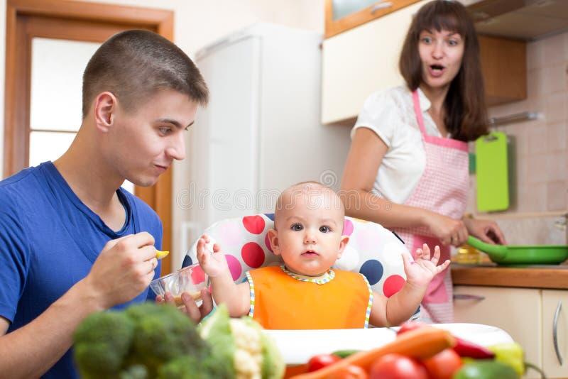 Vader die zijn baby voeden terwijl moeder het koken bij keuken stock afbeeldingen