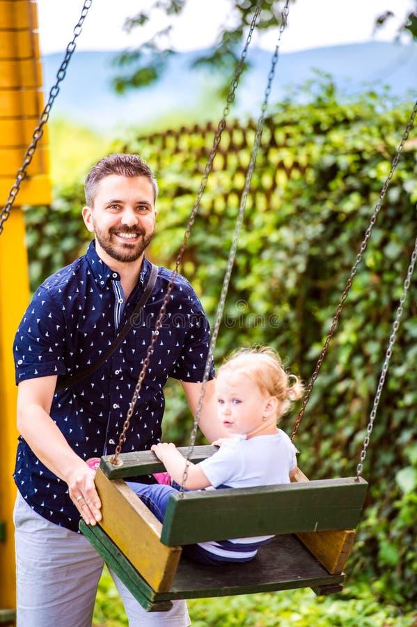 Vader die zijn dochter op schommeling in een park duwen stock foto