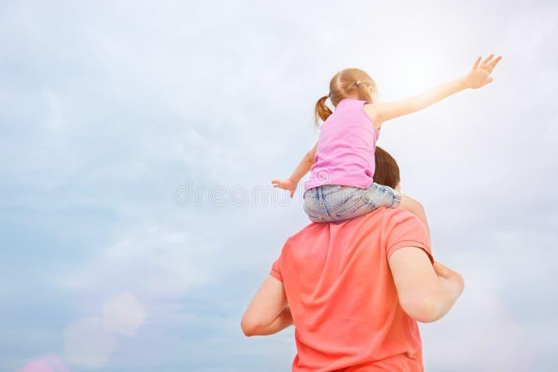Vader die zijn dochter op schouders vervoert royalty-vrije stock foto's