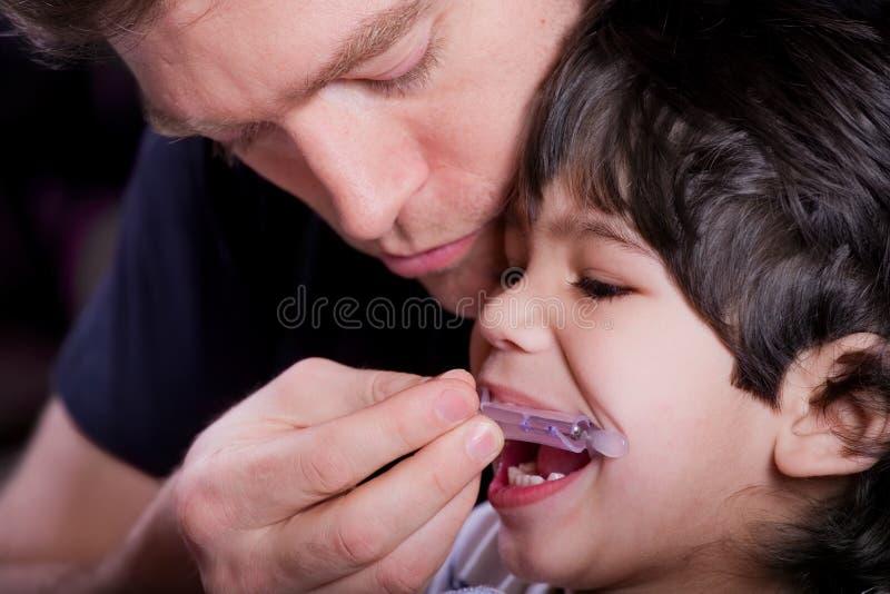 Vader die zijn gehandicapte zoon helpen royalty-vrije stock foto