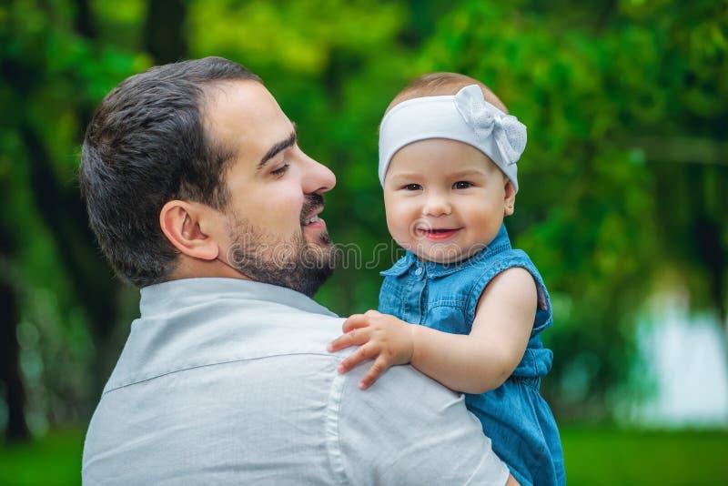 Vader die zijn jonge dochter in het park houden stock fotografie
