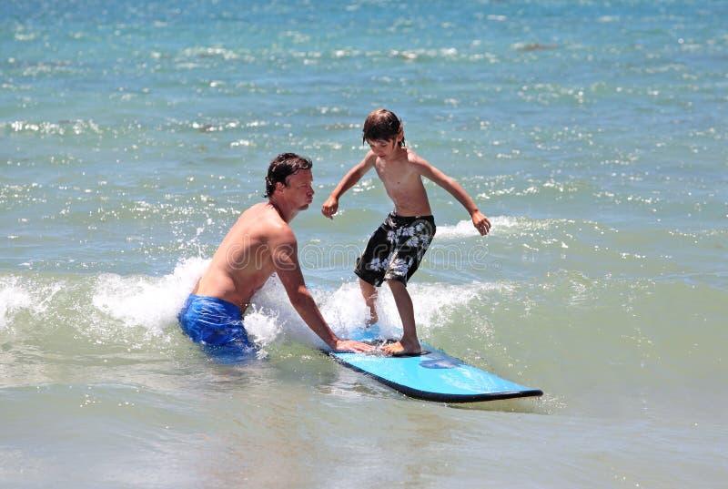 Vader die zijn jonge zoon onderwijst om te surfen royalty-vrije stock foto's