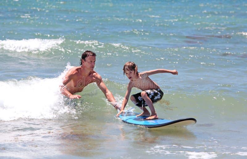 Vader die zijn jonge zoon onderwijst om te surfen stock afbeelding