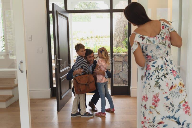 Vader die zijn kinderen omhelzen aangezien hij het huis terwijl moeder ingaat die hen kijken royalty-vrije stock foto
