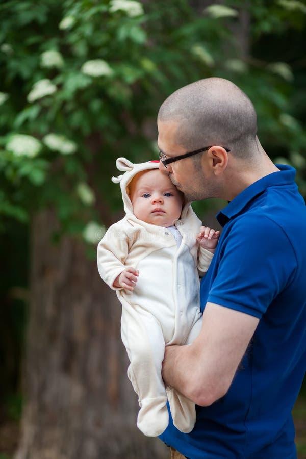 Vader die zijn kleine dochter kust stock foto's