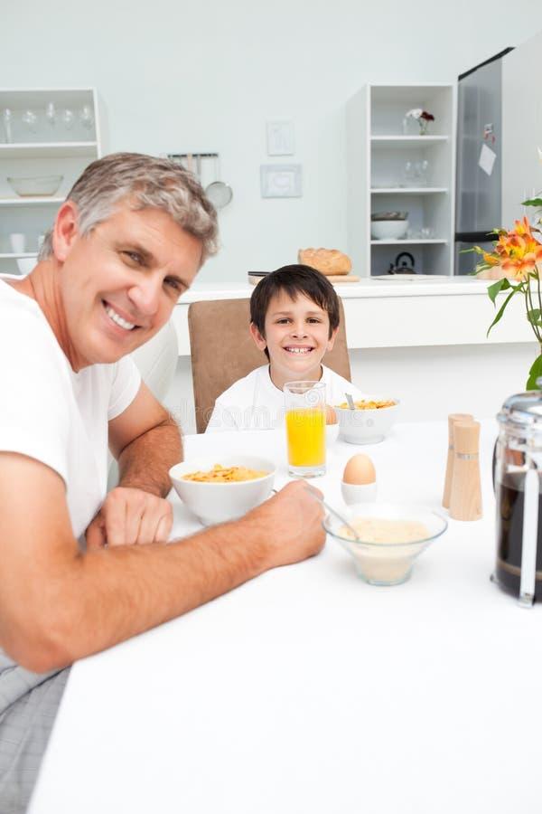 Vader die zijn ontbijt met zijn zoon heeft stock afbeeldingen
