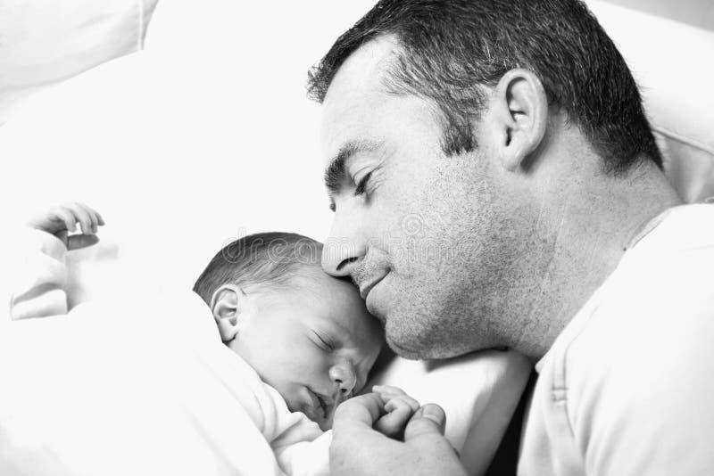 Vader die zijn pasgeboren baby houdt stock afbeeldingen