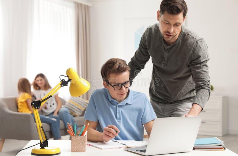 Vader die zijn tienerzoon met thuiswerk helpt stock afbeelding