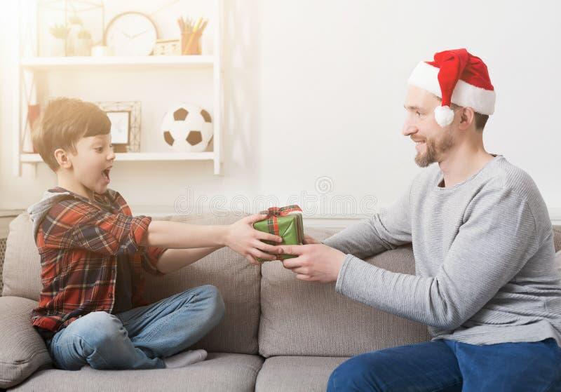 Vader die zijn zoon een Kerstmisheden thuis geven royalty-vrije stock foto