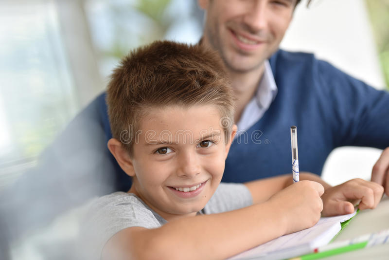 Vader die zijn zoon met thuiswerk helpen stock afbeeldingen