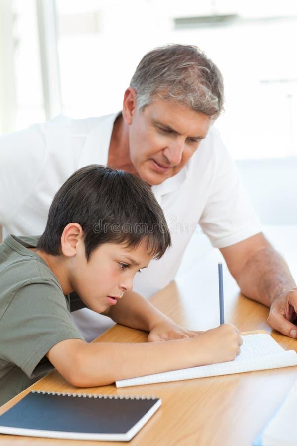 Vader die zijn zoon met zijn thuiswerk helpt stock foto