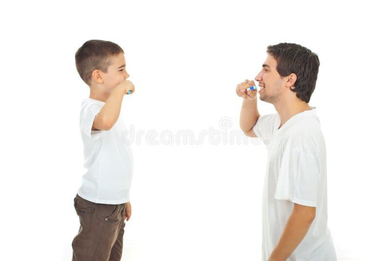 Vader die zijn zoon onderwijst aan het borstelen van tanden royalty-vrije stock fotografie