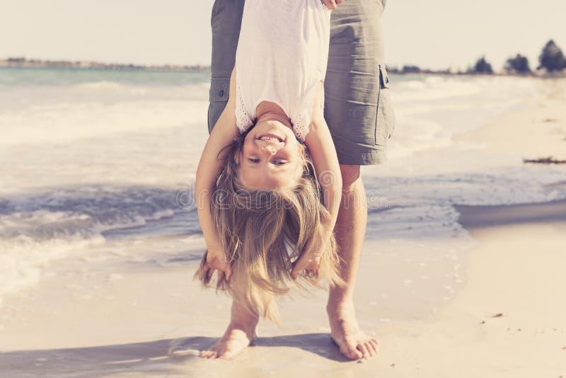 Vader die zoete jonge en mooie blonde kleine dochter houden die door haar voeten hebbend pret op het strand in papa en meisjelief royalty-vrije stock afbeelding