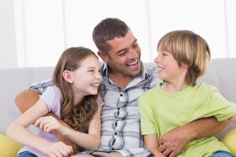 Vader die zoon en dochter kietelen terwijl het zitten op bank royalty-vrije stock afbeelding