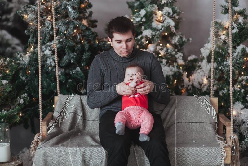 Vader en 1 éénjarige zoon het spelen voor Kerstboomzitting op houten schommeling in studio stock fotografie
