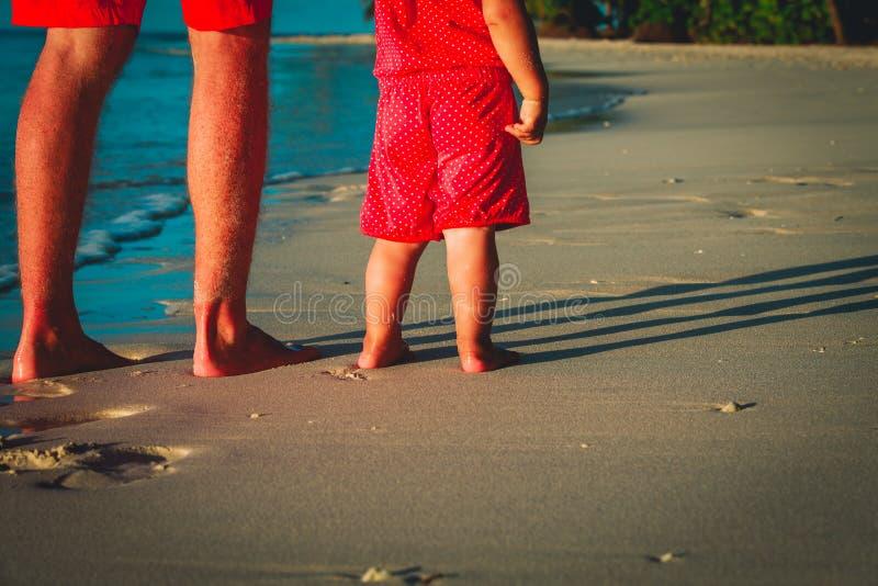 Vader en baby die op zandstrand lopen stock fotografie