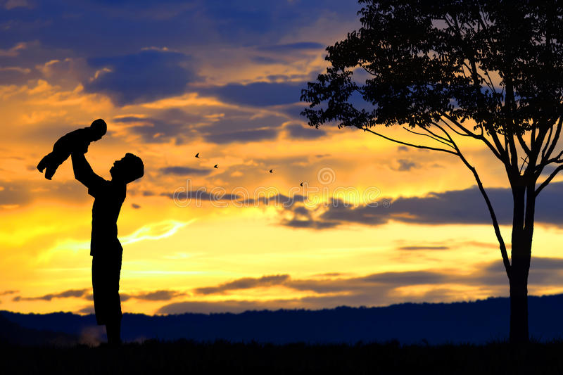 Vader en babysilhouettenspel bij zonsondergangbergen vage achtergrond royalty-vrije stock foto's