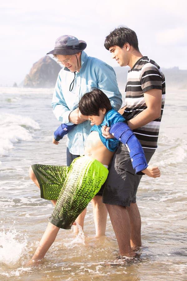 Vader en broer die gehandicapte jongensgang in oceaanwateren helpen royalty-vrije stock afbeelding
