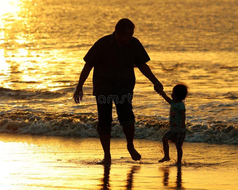Vader en dauther holdingshanden en het spelen bij het strand in Bali, Indonesië tijdens een gouden zonsondergang Oceaan zoals gou royalty-vrije stock afbeelding